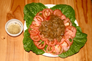 Plate over the bed of tomatoes and lettuce.